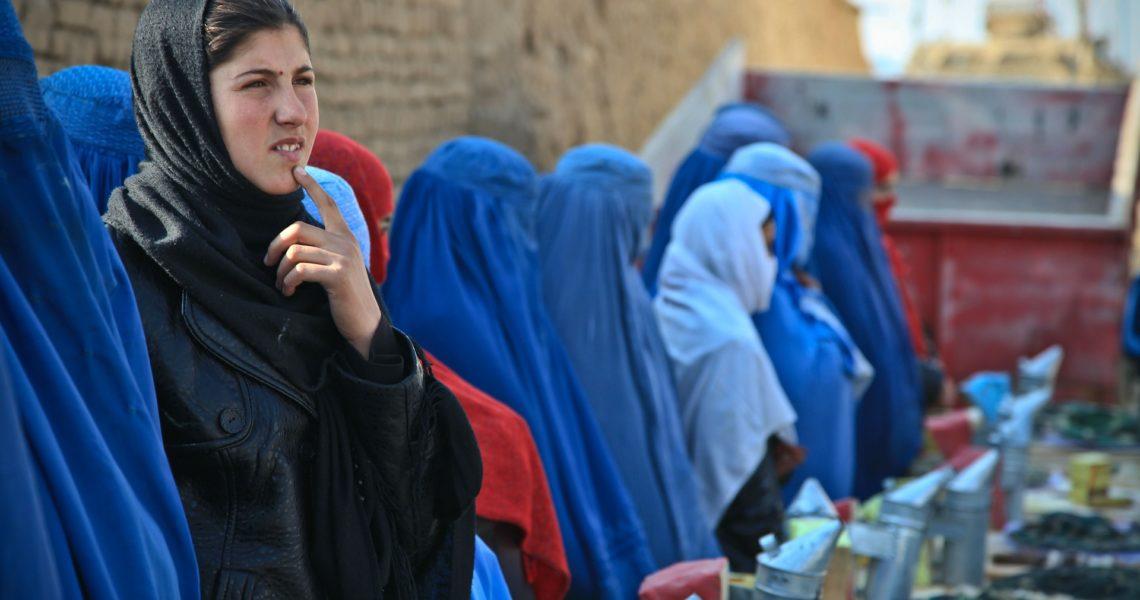 inmitten von vollverschleierten Frauen mit Burka steht eine nachdenkliche Frau.